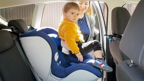 Smiling young woman seating her baby boy in car. Young women seating her baby boy in car Stock Photo