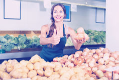 Smiling young woman seller showing yellow onions Royalty Free Stock Photo