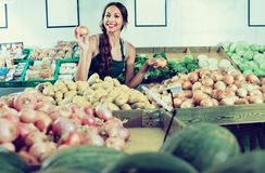 Smiling young woman seller showing yellow onions Stock Image