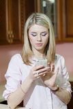 Smiling young woman sending a text message at home Royalty Free Stock Photos