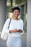 Smiling young woman sending text message int he city Royalty Free Stock Images