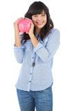 Smiling young woman shaking her piggy bank Stock Image