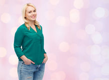 Smiling young woman in shirt and jeans Stock Photography