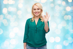 Smiling young woman in shirt showing ok hand sign. Female, gender, gesture, plus size and people concept - smiling young woman in shirt and jeans showing ok hand Royalty Free Stock Image
