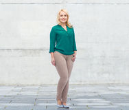 Smiling young woman in shirt and trousers Stock Photos