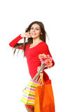 Smiling young woman with shopping bags and a bouquet of gerbers Royalty Free Stock Images