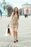 Smiling  young woman with shopping bags  in the city Royalty Free Stock Image