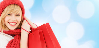 Smiling young woman with shopping bags. Happiness, winter holidays, christmas and people concept - smiling young woman in hat and scarf with shopping bags over stock photos