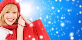 Smiling young woman with shopping bags. Happiness, winter holidays, christmas and people concept - smiling young woman in hat and scarf with shopping bags over royalty free stock images