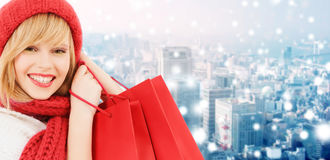 Smiling young woman with shopping bags. Happiness, winter holidays, christmas and people concept - smiling young woman in hat and scarf with shopping bags over royalty free stock photos