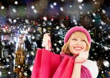 Smiling young woman with shopping bags. Happiness, winter holidays, christmas and people concept - smiling young woman in hat and scarf with pink shopping bags royalty free stock image