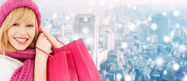 Smiling young woman with shopping bags. Happiness, winter holidays, christmas and people concept - smiling young woman in hat and scarf with pink shopping bags stock photography