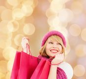 Smiling young woman with shopping bags. Happiness, winter holidays, christmas and people concept - smiling young woman in hat and scarf with pink shopping bags royalty free stock photo