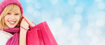 Smiling young woman with shopping bags. Happiness, winter holidays, christmas and people concept - smiling young woman in hat and scarf with pink shopping bags stock photos
