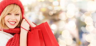 Smiling young woman with shopping bags. Happiness, winter holidays, christmas and people concept - smiling young woman in hat and scarf with red shopping bags royalty free stock image
