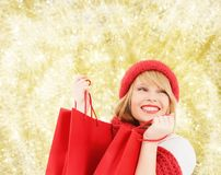 Smiling young woman with shopping bags. Happiness, winter holidays, christmas and people concept - smiling young woman in hat and scarf with red shopping bags stock images