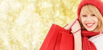Smiling young woman with shopping bags. Happiness, winter holidays, christmas and people concept - smiling young woman in hat and scarf with red shopping bags stock image