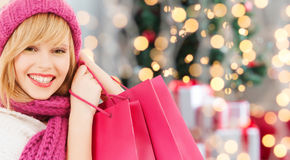 Smiling young woman with shopping bags. Happiness, winter holidays and people concept - smiling young woman in hat and scarf with pink shopping bags over stock photo