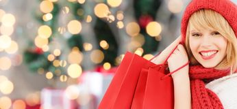 Smiling young woman with shopping bags. Happiness, winter holidays and people concept - smiling young woman in hat and scarf with red shopping bags over Royalty Free Stock Photos