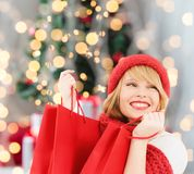 Smiling young woman with shopping bags. Happiness, winter holidays and people concept - smiling young woman in hat and scarf with red shopping bags over royalty free stock photography