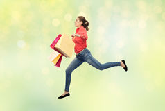 Smiling young woman with shopping bags jumping Stock Image