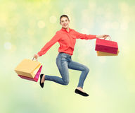 Smiling young woman with shopping bags jumping Royalty Free Stock Image
