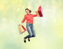 Smiling young woman with shopping bags jumping Stock Photography