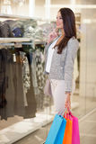 Smiling young woman with shopping bags in mall Royalty Free Stock Image