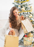 Smiling young woman with shopping bags near christmas tree Royalty Free Stock Photography