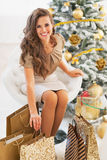 Smiling young woman among shopping bags near christmas tree Stock Image