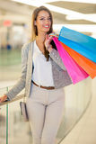 Smiling young woman with shopping bags over mall background Stock Photo