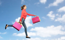 Smiling young woman with shopping bags running Stock Photos