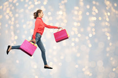 Smiling young woman with shopping bags running Stock Photo