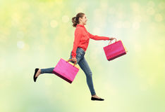 Smiling young woman with shopping bags running Royalty Free Stock Photos