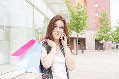 Smiling young woman with shopping bags talking by phone. Stock Photo
