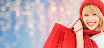 Smiling young woman with shopping bags. Winter holidays, christmas and people concept - smiling young woman in hat and scarf with red shopping bags over lights royalty free stock photo