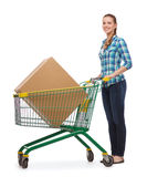 Smiling young woman with shopping cart and big box. Happiness, shopping and people concept - smiling young woman with shopping cart and big box in it Royalty Free Stock Images