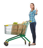 Smiling young woman with shopping cart and food. Happiness, shopping and people concept - smiling young woman with shopping cart and food in it showing thumbs up Royalty Free Stock Photo