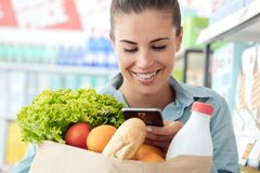 Woman shopping and texting with her phone royalty free stock photos