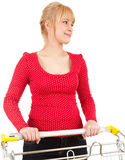 Smiling young woman with shopping trolley Royalty Free Stock Photography