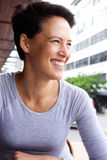 Smiling young woman with short hair smiling in the city Royalty Free Stock Photography