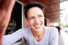Smiling young woman with short hair taking selfie stock photography