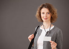 Smiling young woman showing badge Royalty Free Stock Photography