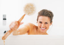 Smiling young woman showing body brush in bathtub Royalty Free Stock Photos