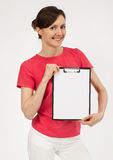 Smiling young woman showing clipboard Stock Image