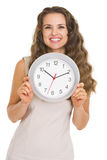 Smiling young woman showing clock Stock Photos