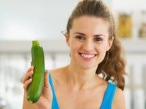 Smiling young woman showing fresh zucchini Stock Image