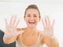 Smiling young woman showing hands with soap foam Royalty Free Stock Image