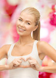 Smiling young woman showing heart shape gesture Stock Images