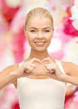 Smiling young woman showing heart shape gesture Stock Photography